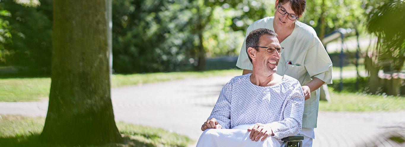 Pflegepersonal mit Patient im Kurpark nahe der Beckerklinik