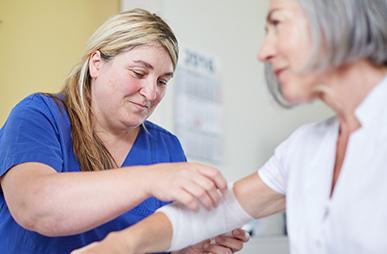Mitarbeiterin der Beckerklinik legt Patientin einen Verband an